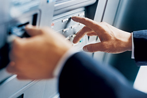 Hand pressing a button on an automated teller machine (ATM)