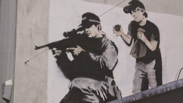 The image, featuring a police sniper about to be surprised by a boy bursting a paper bag