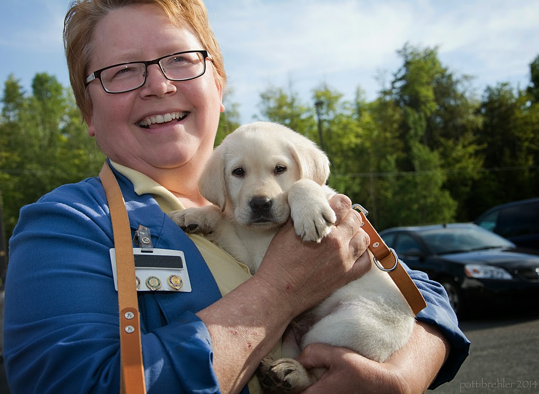 A woman wearing glasses and short hair, wearing a blue jacket is holding a small yellow lab in her arms. She is smiling at the camera and the puppy is looking at the camera too.