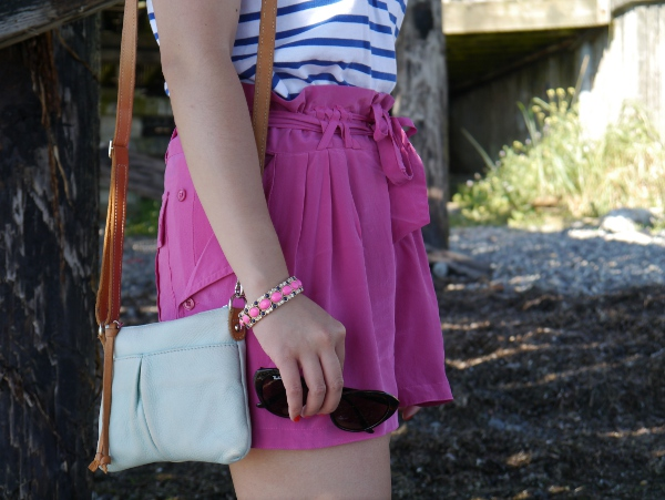 A more detailed view of a striped tee worn with fuchsia silk shorts, bracelet, and a small but colourful crossbody bag and cat-eye shades.