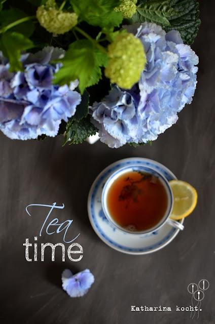 Tea Time blaue Hortensien und Schneeball in weißer Vase, blaue Teetasse Sammeltasse mit Schwarztee, Zitrone