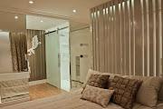 A bancada do banheiro fica integrada ao quarto e disfarçada por paredes .