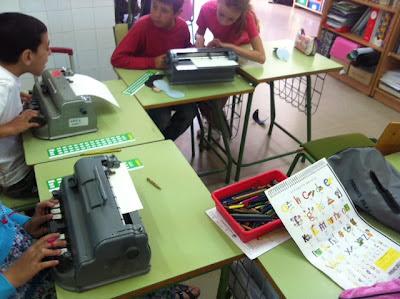 La foto muestra a varios alumnos trabajando con máquinas perkins para conocer el sistema braille.