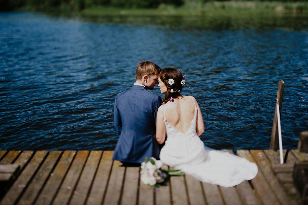 Sofie och Erik sitter på brygga med brudbukett