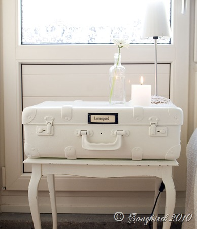 This white vintage suitcase paired with a simple candle and flower vase is calming and serene.