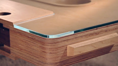 Close up of right bottom corner showing glass top and layers of plywood for body