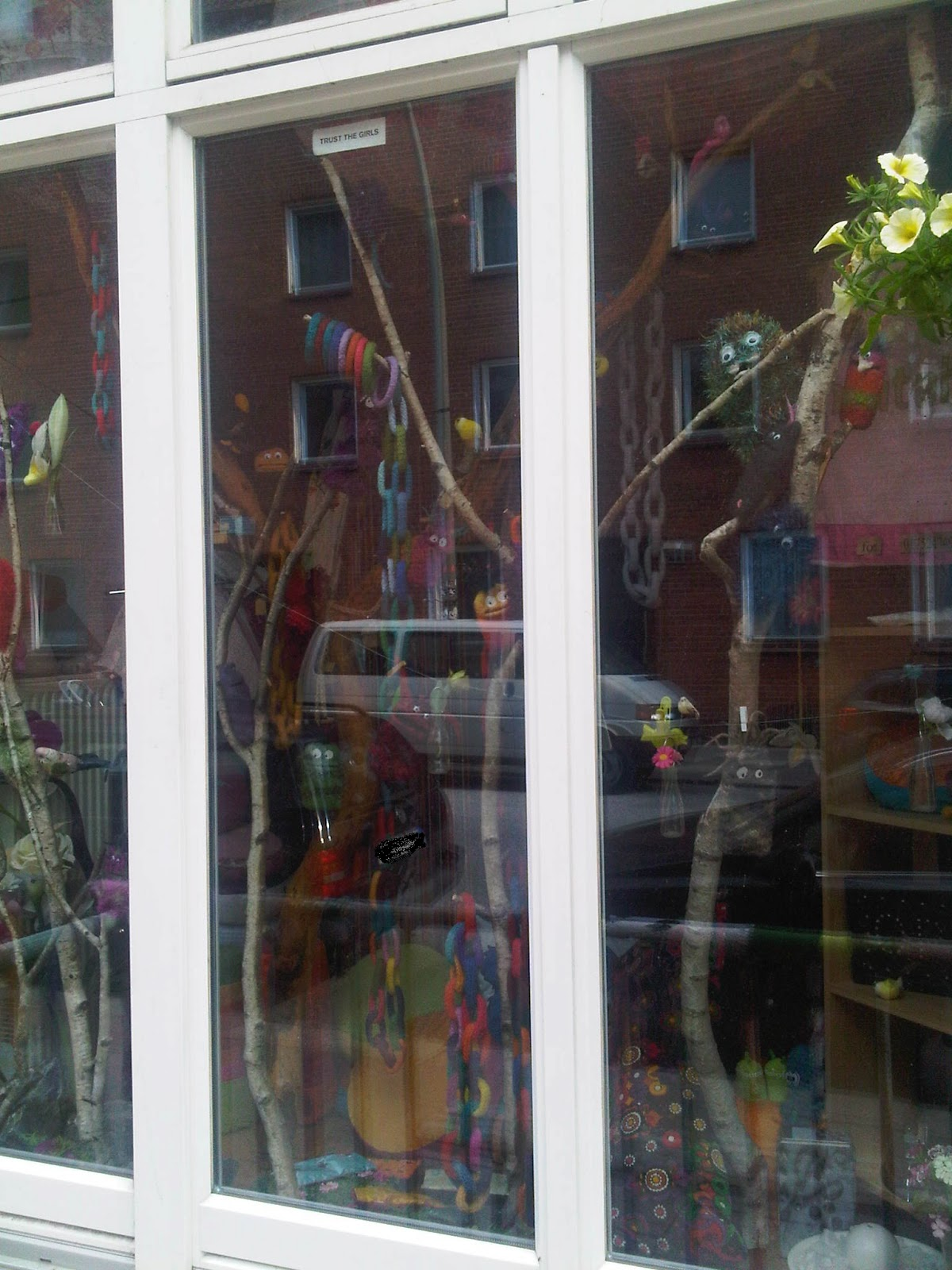 Schaufenster mit Strickwaren. Strickfiguren, Ästen zur Deko mit Strickwaren.