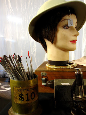 Corner of a market stall with a container of sculpting tools for sale, along with a mannequin head wearing a pith helmet, and a microscope.