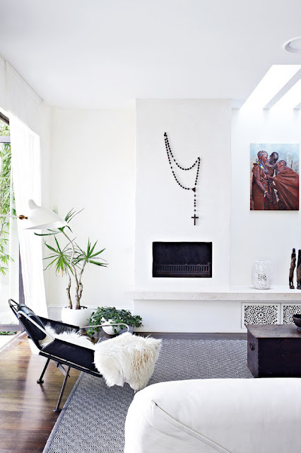 Living room with white washed walls with prayer beads as wall hanging, fireplace, dark wood floor and a patterned rug