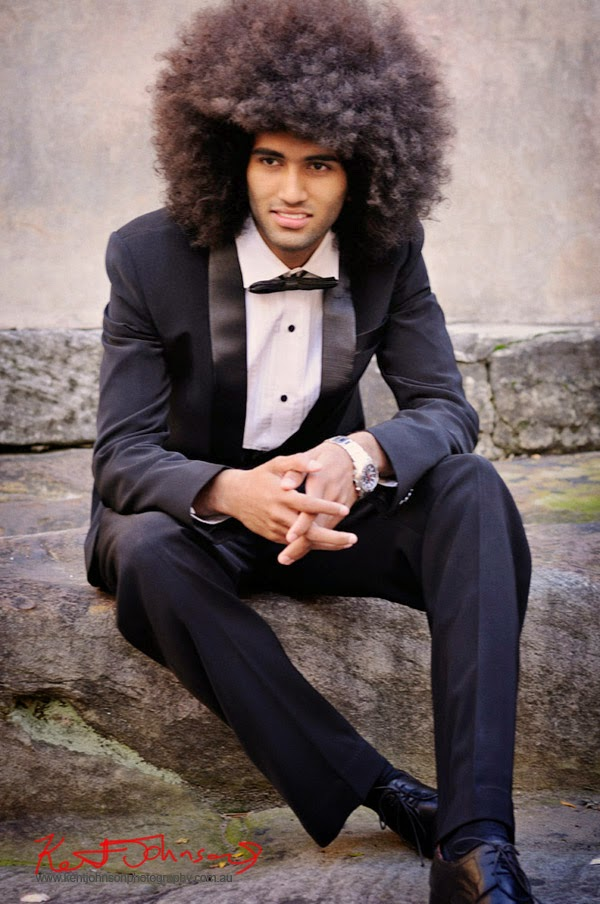 Kyrien sitting in a Tuxedo photographed against a weathered old wall in Sydney. Male modelling portfolio photographed by Kent Johnson.