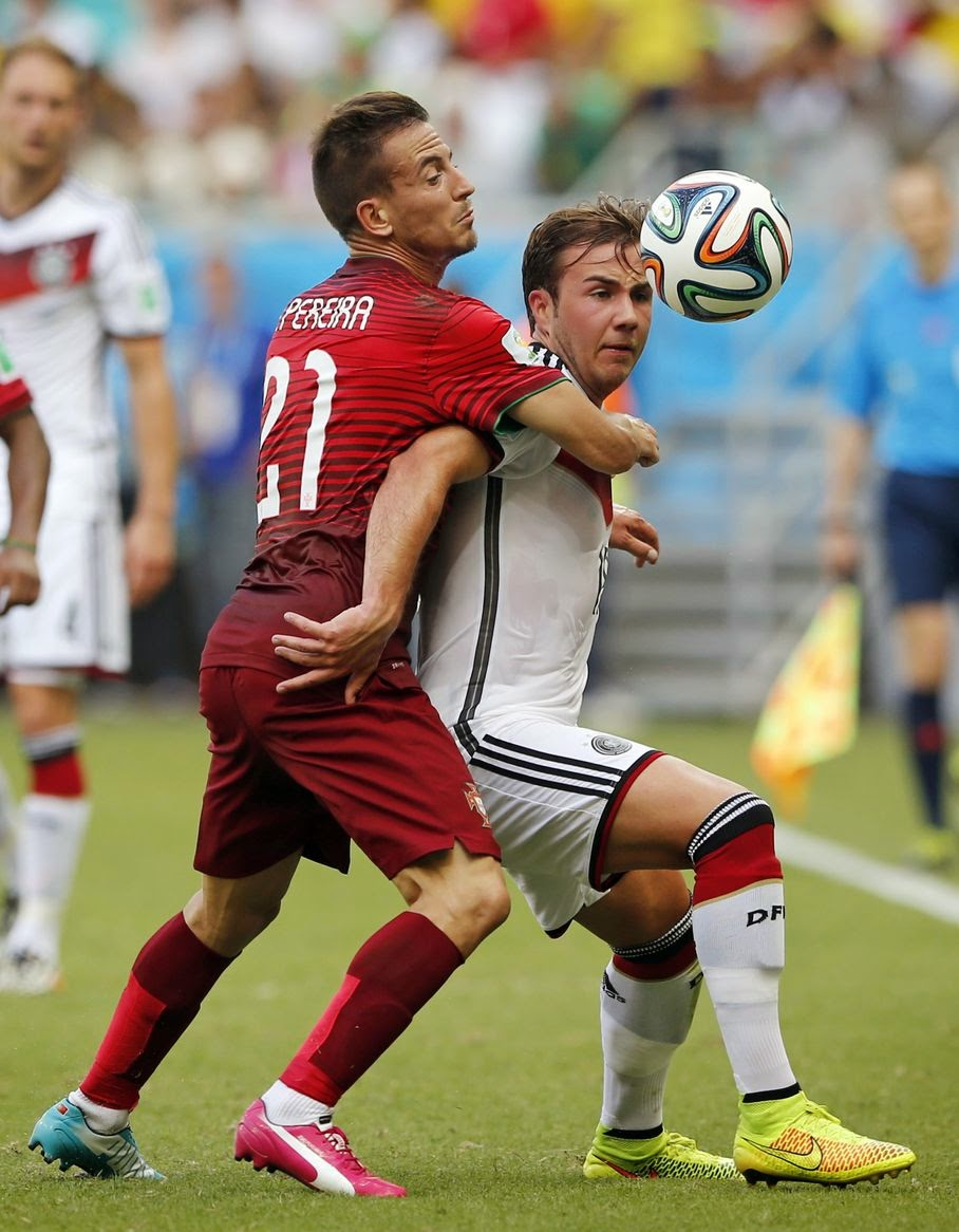 Portugal's Joao Pereira, left, challenges Germany's Mario Goetze during the group G World Cup soccer match between Germany and Portugal at the Arena Fonte Nova in Salvador, Brazil, Monday, June 16, 2014.