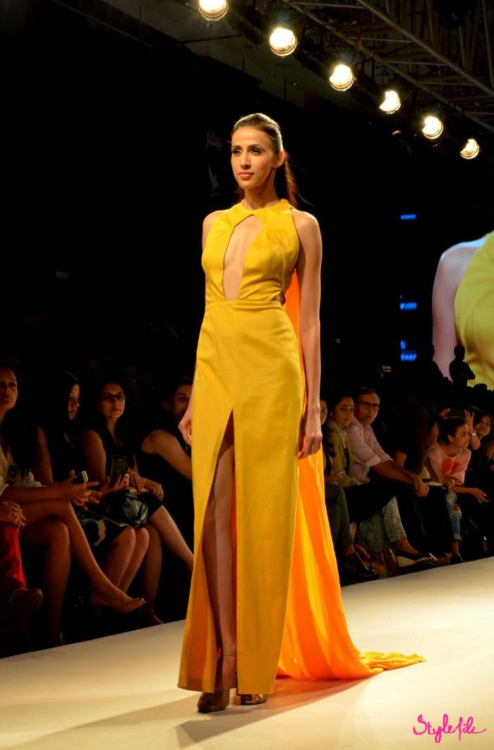 Model showcases a bright mango yellow gown with slit by designer Nikhil Thampi at Lakme Fashion Week Summer Resort 2015 in Mumbai