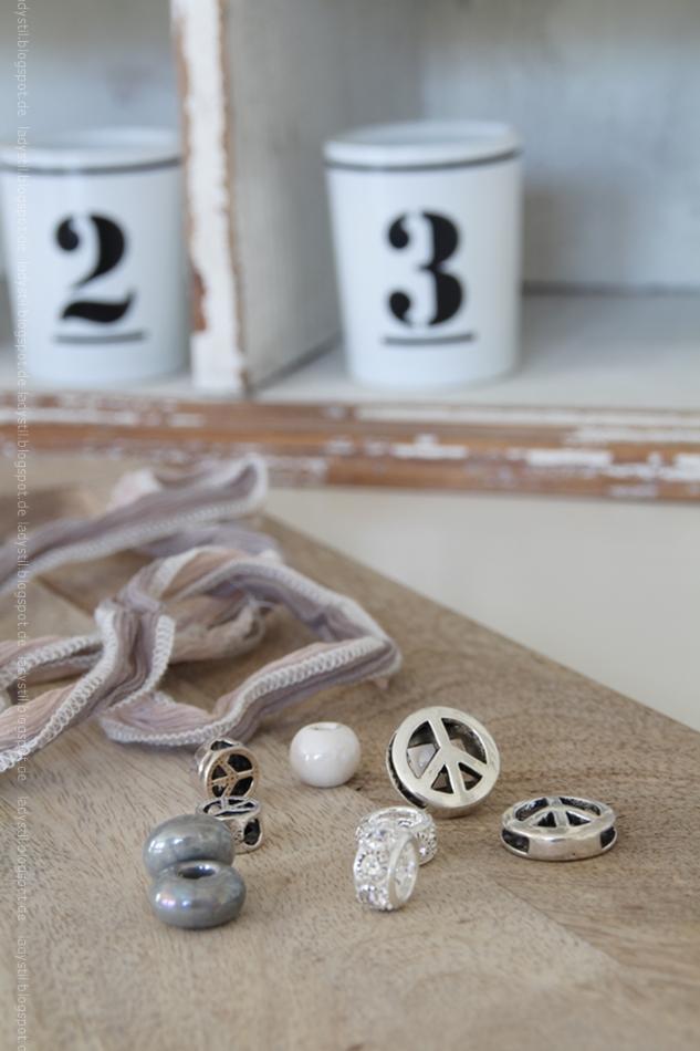 auf einem höölzernen Brett liegt ein beiges Seidenband mit verschiedenen Armbandanhängern