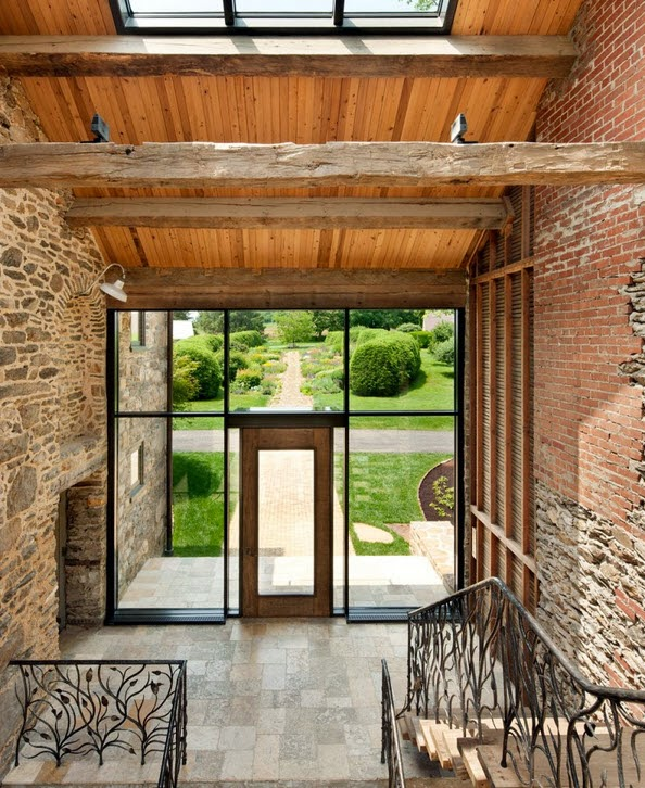 techo y vigas de madera puedes ver el trabajo del de las barandas de la escalera en hierro y al final la puerta dentro de grandes vidrios traslucidos