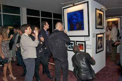 "Guest admire a blue tinted portrait of Cyndi Lauper  entitled ""Kitten"""