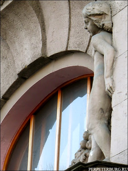 Скульптуры детей над входом в парадную в Санкт-Петербурге