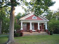 foto de fachada de casa roja con columnas blancas