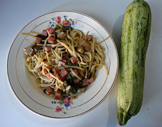 Plato de pastas con salsa y al lado un zucchini entero