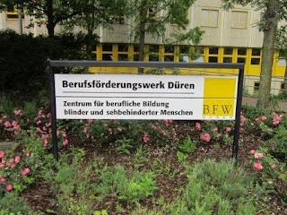 """fotografia do cartaz na entrada do """"Berufsförderungswerk Düren"""""""