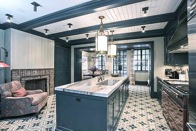 Blue and grey kitchen with brick fireplace and marble countertops in Steven Gambrel's home