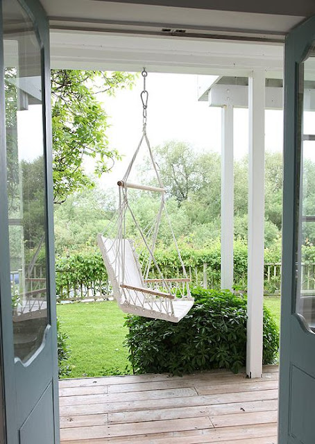 backyard patio with woven porch swing