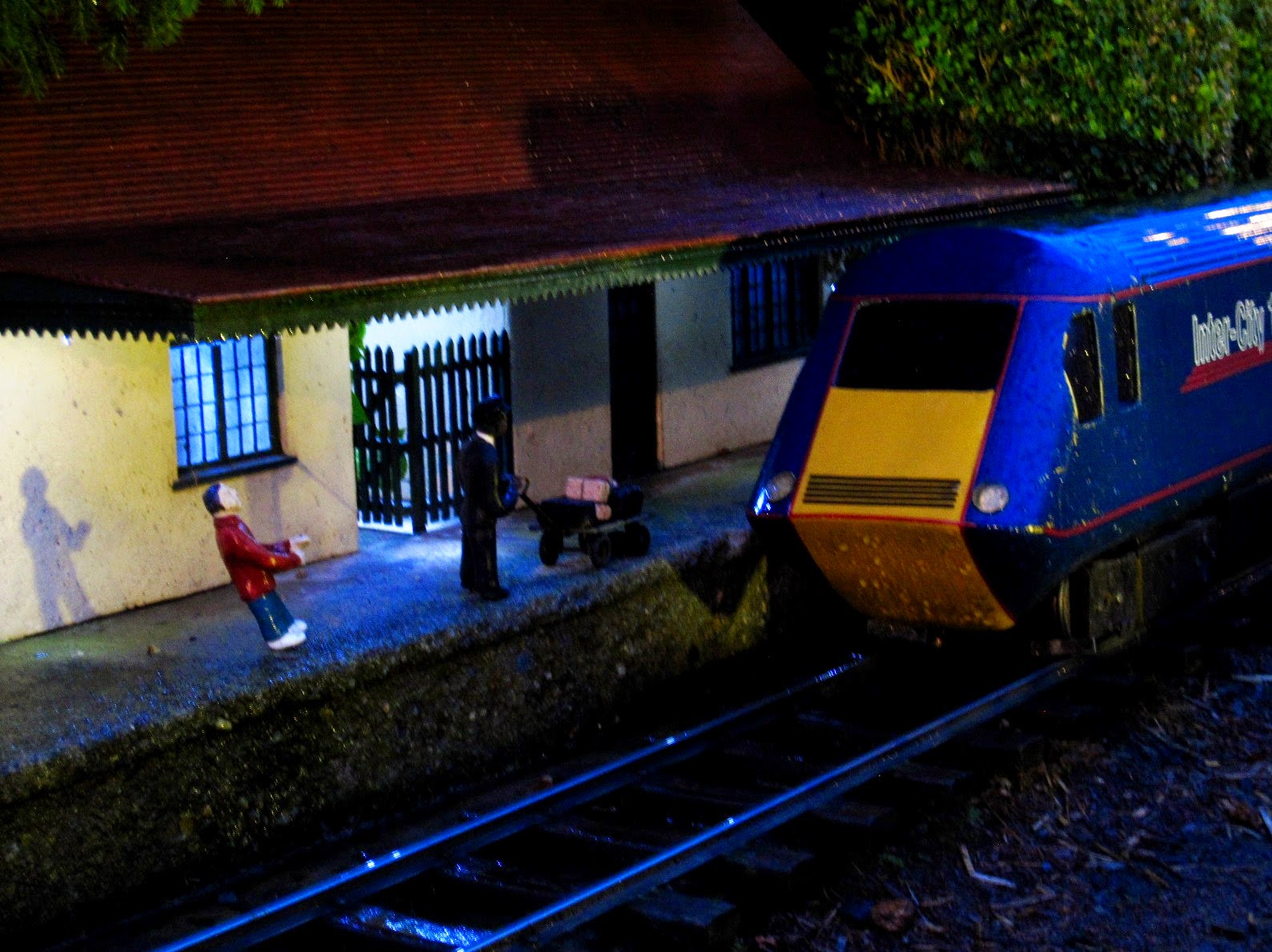 Miniature model of a railways station with a train at the station, at night.