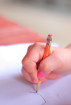 image of a hand writing with a pencil