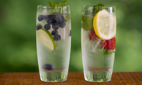 Two glasses of enhanced water with berries and herbs for flavor and color.