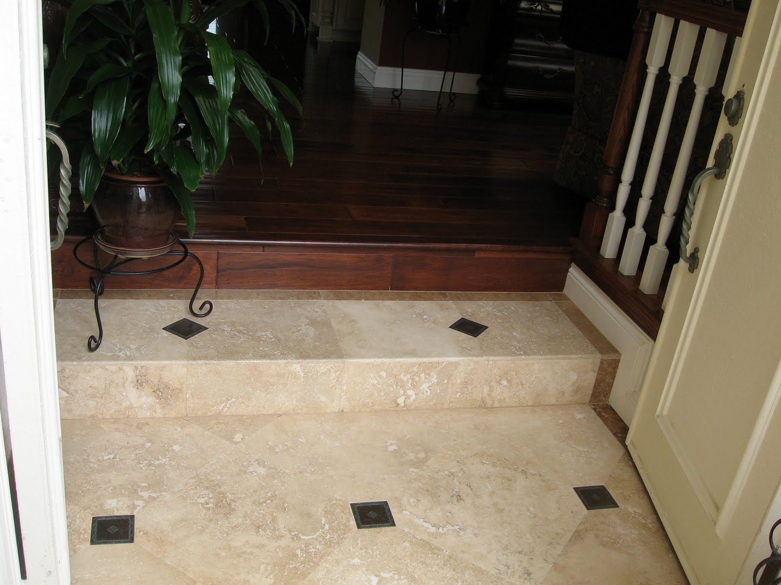 Travertine flooring in the entrance was inlayed with bronze accent  title=