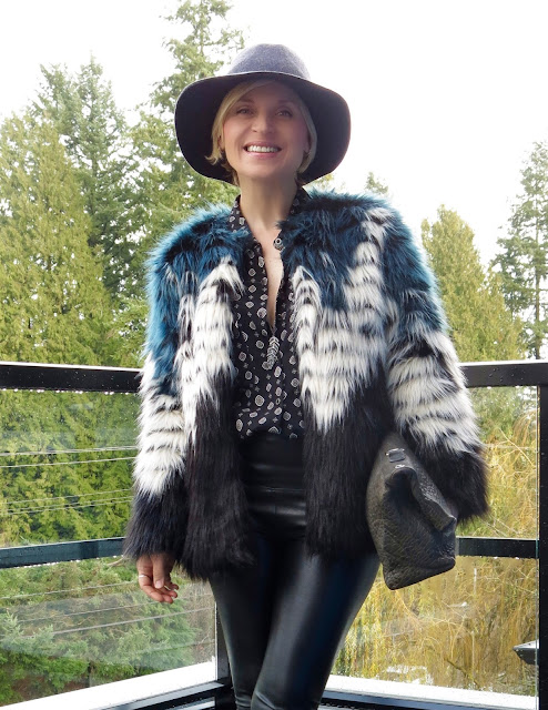 faux-fur jacket, patterned shirt, vegan leather leggings, and a floppy hat
