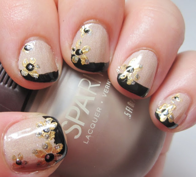 Gold flowers over a black French tip and nude nail with topcoat