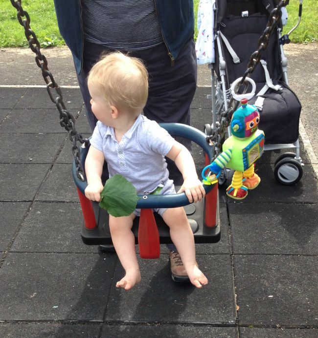 Baby in swing looking right with adult stood behind