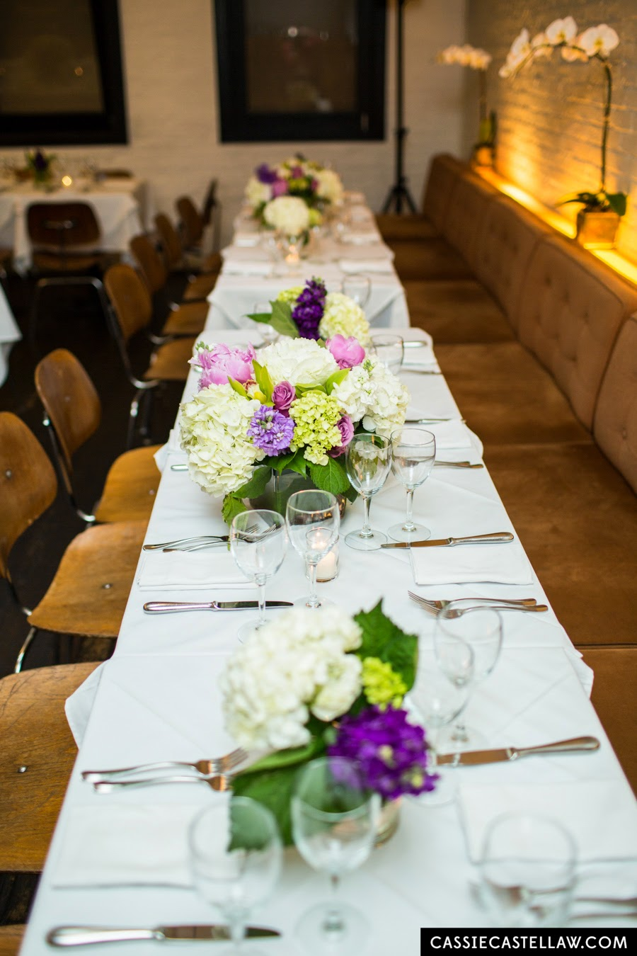 Romantic floral centerpieces on long white table: White and green hydrangea, pink roses, pink peony, green orchid, delicate purple flowers. NYC Lifestyle wedding photography by Cassie Castellaw. www.cassiecastellaw.com