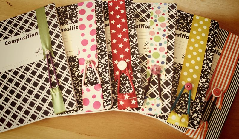 Black-and-white composition books with wrap-around ribbon bookmarks. Each bookmark features an elastic hair-tie secured by a casing sewn in the lower portion of ribbon that is visible. The hair-ties are stretched up to loop over buttons sewn to the other end of ribbon.
