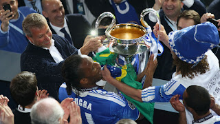 Chelsea FC owner Roman Abramovic (L) and Didier Drogba celebrate with the UEFA Champions League trophy after victory in the UEFA Champions League final