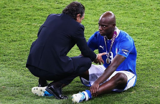 Italy forward Mario Balotelli looks dejected as he speaks with his coach Cesare Prandelli