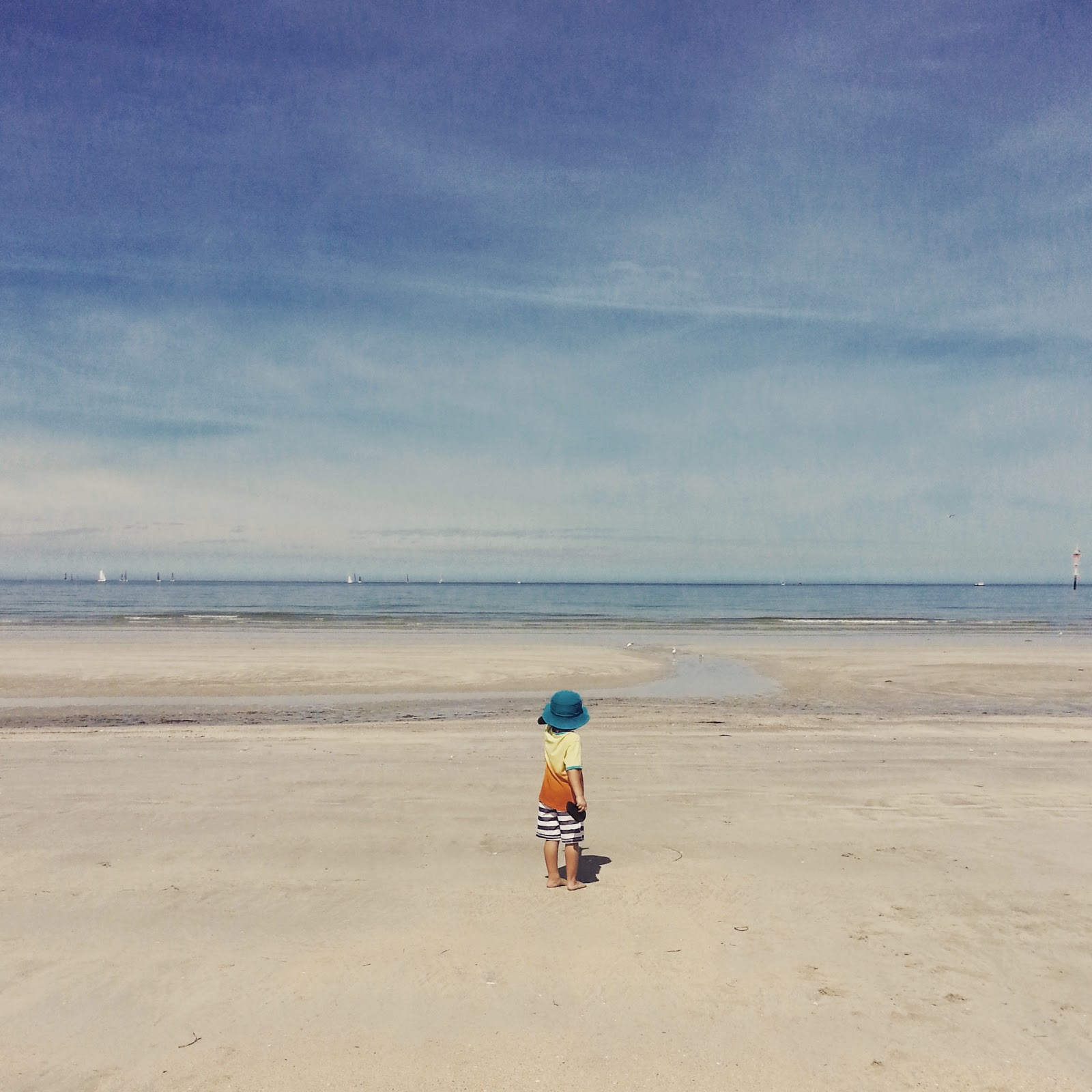 beach scene with sunny blue skies, calm blue ocean, saing boats and little boy pointing out to sea