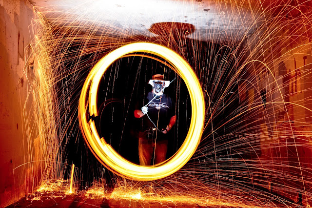 A guy wearing a creepy gas mask while twirling some burning steel wool from a chain.
