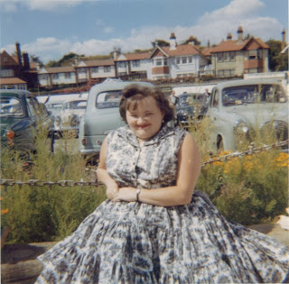 colour picture of my mum sitting on a wall wearing a flowing colourful dress.