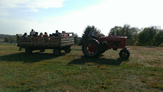 a tractor pulling a cart full of people on a hay ride