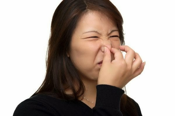 Woman holding her nose due to bad smell