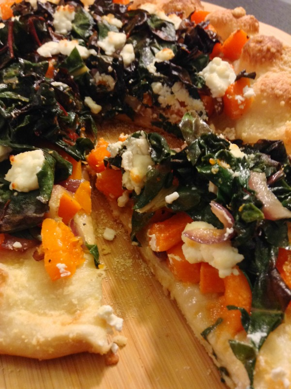 Slice of Roasted Butternut Squash and Onion Pizza with Swiss Chard and Goat Cheese