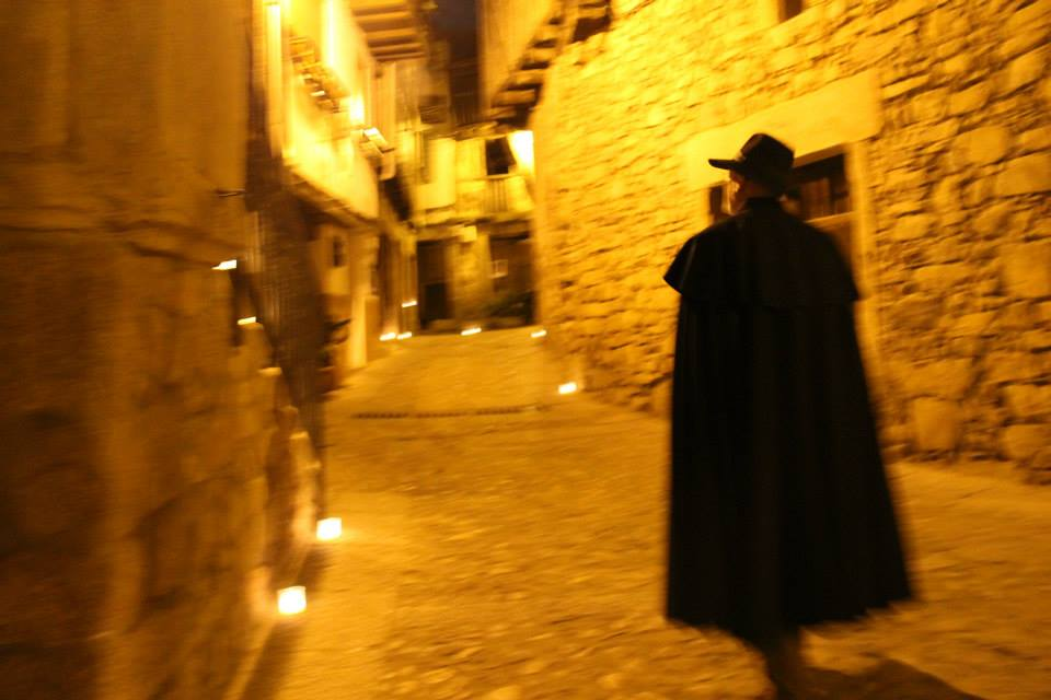 Un mogarreño, con capa y sombrero , camina entre la luz cálida de las velas en una calle de la villa de Mogarraz