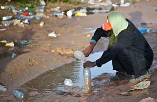 Photo : Refugee from Libya getting water from a puddle