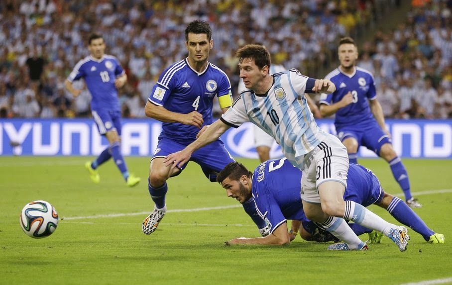Argentina's Lionel Messi (10) scrambles to get back to the ball against Bosnia defenders Emir Spahic (4) and Sead Kolasinac (5) during their group F World Cup soccer match at the Maracana Stadium in Rio de Janeiro, Brazil, Sunday, June 15, 2014.