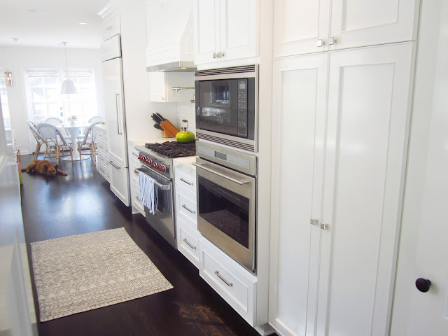 gallery kitchen with stainless steel appliance oven, white panel hood, refridgerator, pantry, dark wood floors with a view of the breakfast nook