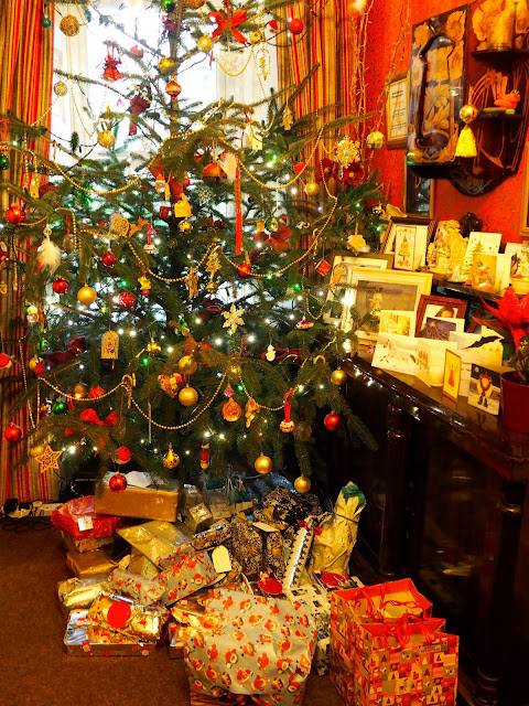 Christmas tree with presents underneath and cards on the sideboard