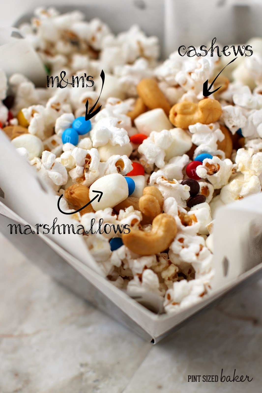 Popcorn mixed with Salty Cashews, Sweet mini marshmallows and M and M's and tossed with butter. A quick and easy snack!