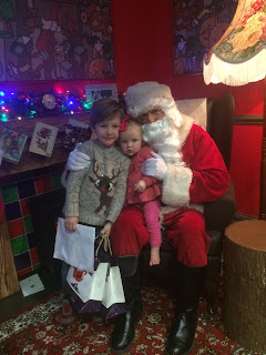 Small boy and baby girl meet Santa