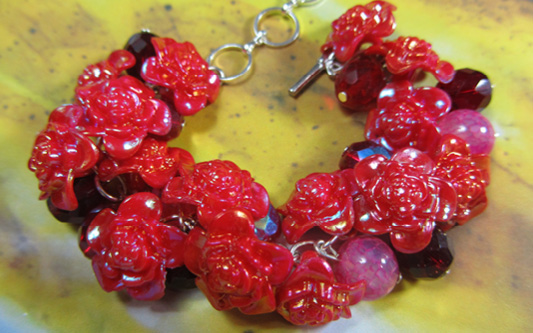 Dramatic bracelet has red flower buttons, shiny czech beads and dragon veins agate